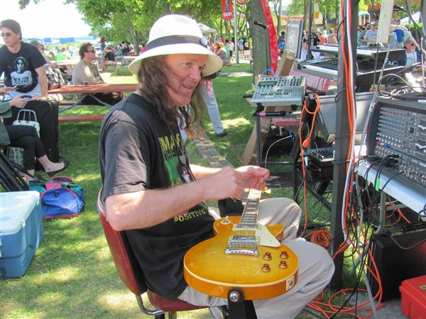 Artist and Stage Manager at The Renegade Stage Coventry Jones restrings his guitar in between performances