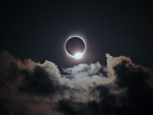 "One of the most beautiful sights associated with a total solar eclipse is the ""diamond ring."" It appears just before the beginning of totality, when a single bright point of sunlight—the diamond—shines through a deep valley on the Moon's limb (edge) and the inner corona—the ring—becomes visible. As the diamond vanishes, it's safe to remove your solar filters. A second diamond ring appears at the end of totality when a deep valley on the opposite side of the retreating Moon exposes a single bead of bright sunlight that begins to wash out the corona. Put your filters back on! Credit: Rick Fienberg / TravelQuest International / Wilderness Travel"